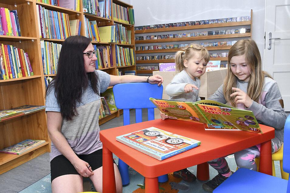 Isabel Graf sowie Pia und Lina im Zimmer mit der Kinderliteratur der Gemeindebibliothek Rietschen.