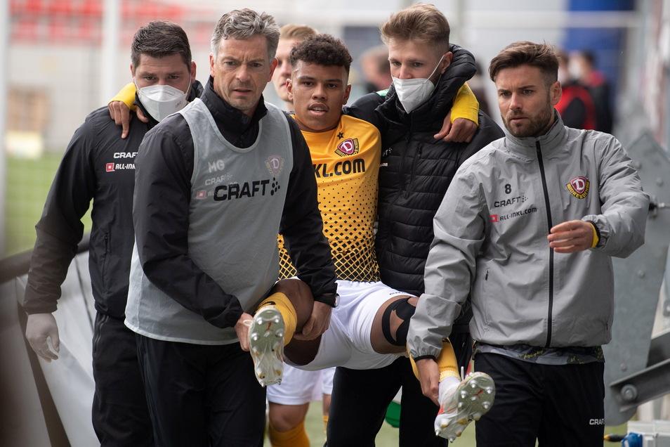 Betreuer und Mitspieler tragen den verletzten Ransford-Yeboah Königsdörffer in Wiesbaden in Richtung Kabine.