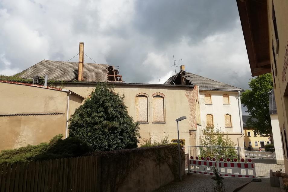Beim rückwärtigen Blick auf die Gebäude sind die Schäden am Dach sichtbar.