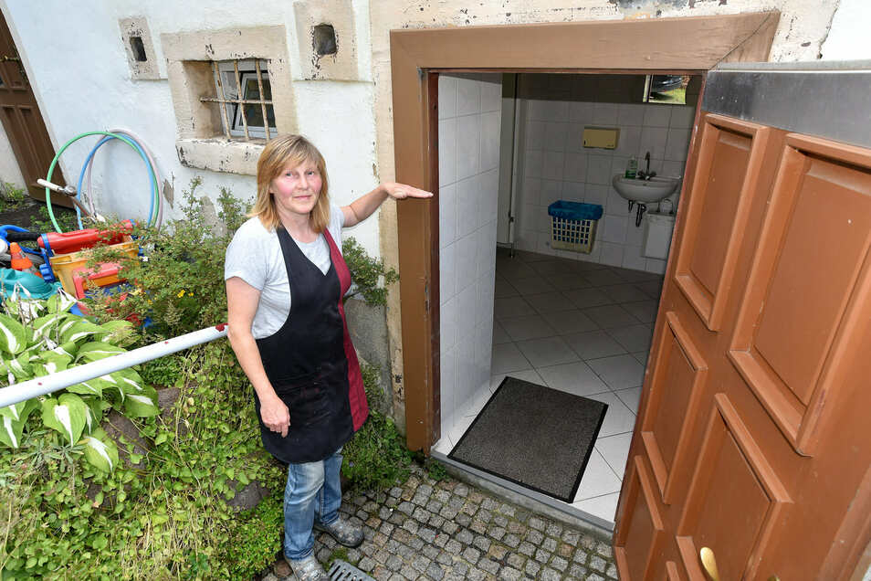 Simone Stegner zeigt, wie hoch das Wasser am 7. August 2010 an dieser Toilette stand.