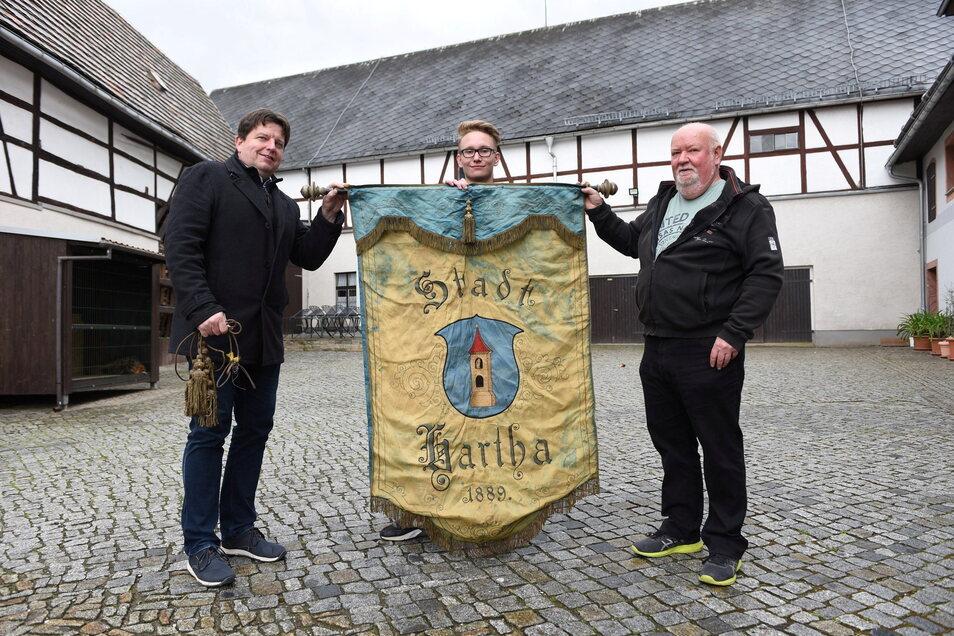 Fritz Schröder (mitte) und Stephan Mathys (rechts) übergaben die historische Fahne an Harthas Bürgermeister Ronald Kunze.