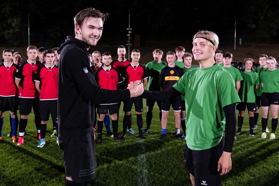 Die Mannschaftskapitäne Richard Geidel (links) vom Joliot-Curie-Gymnasium und Alexander Kania (rechts) vom Augustum-Annen-Gymnasium geben sich vor dem Fußballspiel die Hände.