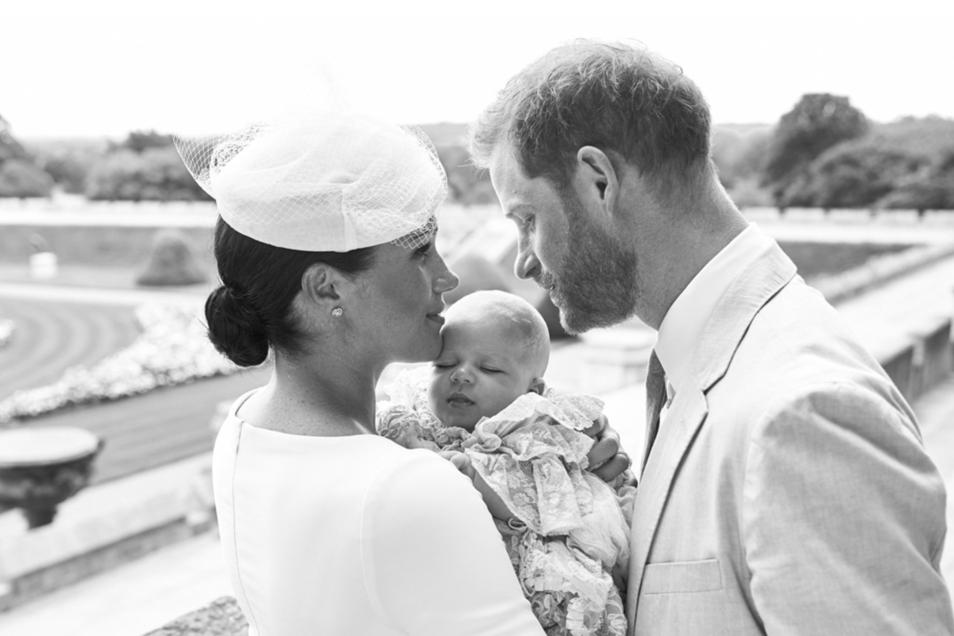 Harry und Meghan im Garten des Schlosses Windsor Castle. Meghan hält den offenbar in seinem voluminösen Taufkleid selig schlummernden Archie im Arm.