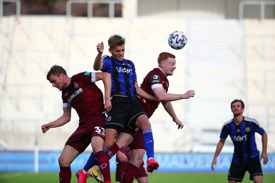 Das Spiel ist hart umkämpft: Nicklas Shipnoski vom 1. FC Saarbrücken nimmt es im Luftkampf gleich mit zwei Dynamos auf: Christoph Daferner (l.) und Paul Will.