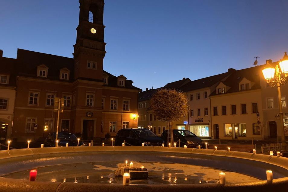 Die Teilnehmer des Spazierganges in Königsbrück stellten ihre Kerzen am Abend auf dem Brunnenrand vor dem Rathaus ab.