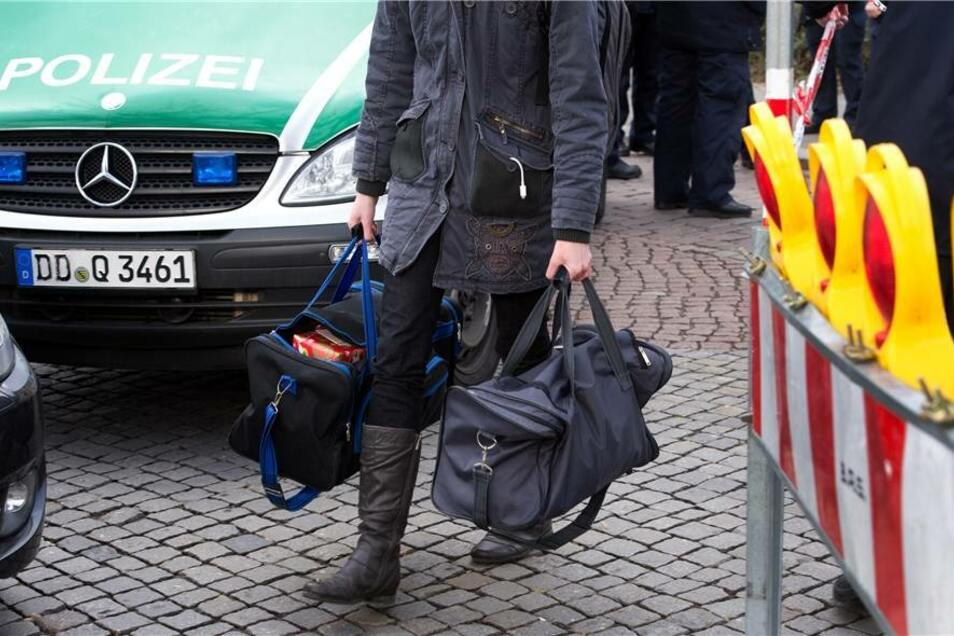 Ein Frau verlässt den Sperrkreis mit zwei Taschen.
