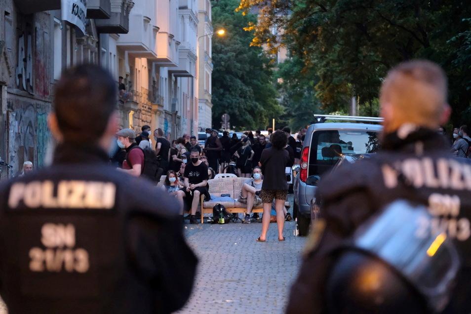 Polizisten stehen an einer Straße im Leipziger Osten vor einem Haus, das von Aktivisten besetzt wurde.