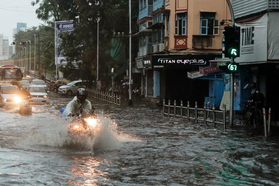 """Pendler fahren in Mumbai auf einer überschwemmten Straße nach starkem Regenfall. Aufgrund des Zyklon """"Tauktae"""" mussten die Behörden hunderttausende Menschen in Sicherheit bringen und die Corona-Impfungen in einem Bundesstaat einstellen."""