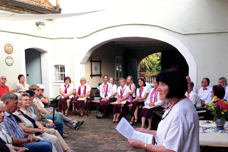 Dora Gebauer trägt Biographisches zu Johann Kasper vor. Hinten wartet der Chor Seidewinkel auf seinen Einsatz.