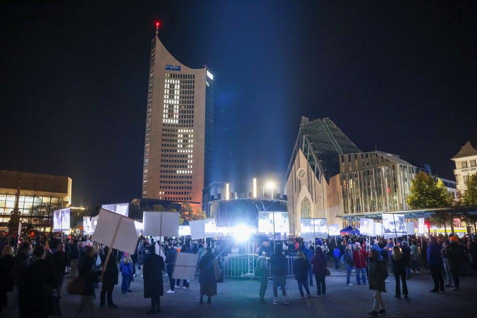 Menschen halten auf dem Augustusplatz im Rahmen einer Videoinstallation Papptafeln in die Höhe, auf die historische Fotos projiziert werden.