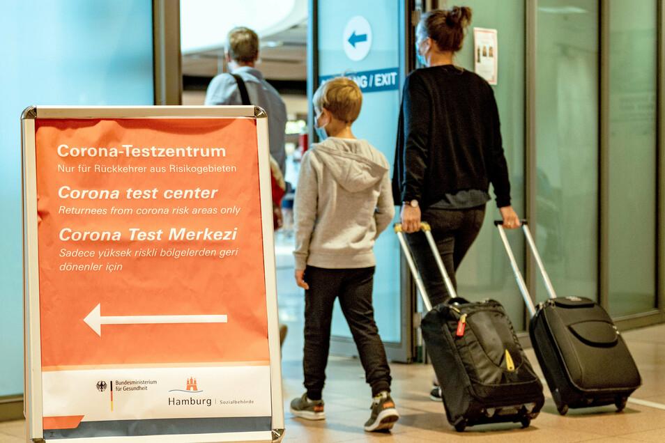 Reisende gehen aus dem Sicherheitsbereich des Hamburger Flughafens an einem Schild vorbei, auf dem die Richtung zum Corona-Testzentrum angezeigt wird.