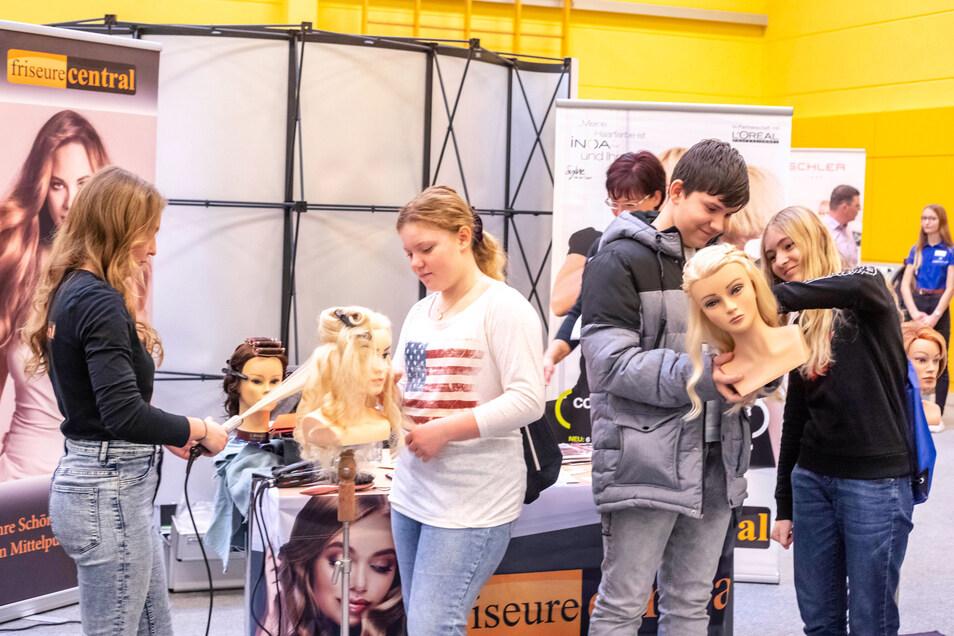 """Das Döbelner Friseurteam von """"Friseure Central"""" bietet die Möglichkeit zum Haarschnitt an einer Puppe. Sara, Jeremy, und Jenny aus Hartha bekamen von Vivien Mai (links) viele nützliche Tipps."""