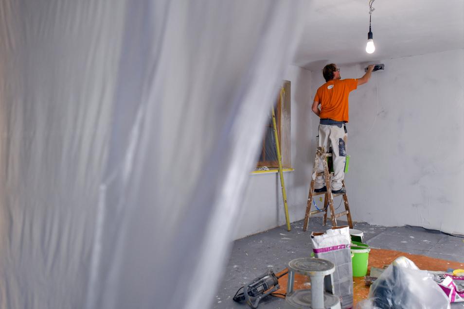 Ein Maler spachtelt die Wände eines Zimmers. Die Auftragsbücher der Handwerker in der Region Döbeln sind trotz Corona-Krise offenbar gut gefüllt.