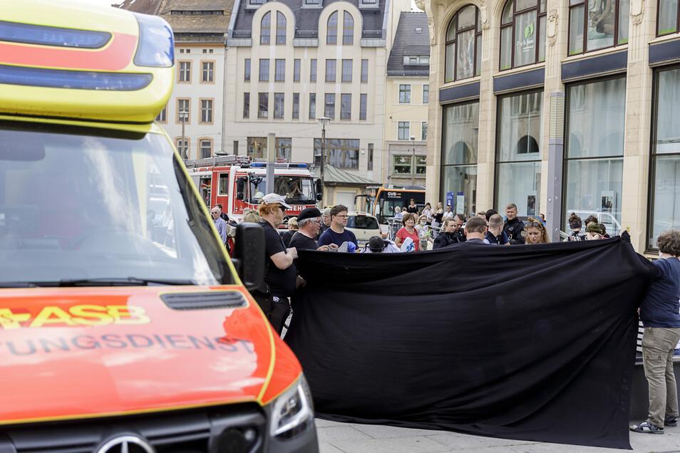 Menschen schirmten den verletzten Mann ab, der gar nichts mit der Demo zu tun hatte. Der Rettungsdienst kümmerte sich um ihn.