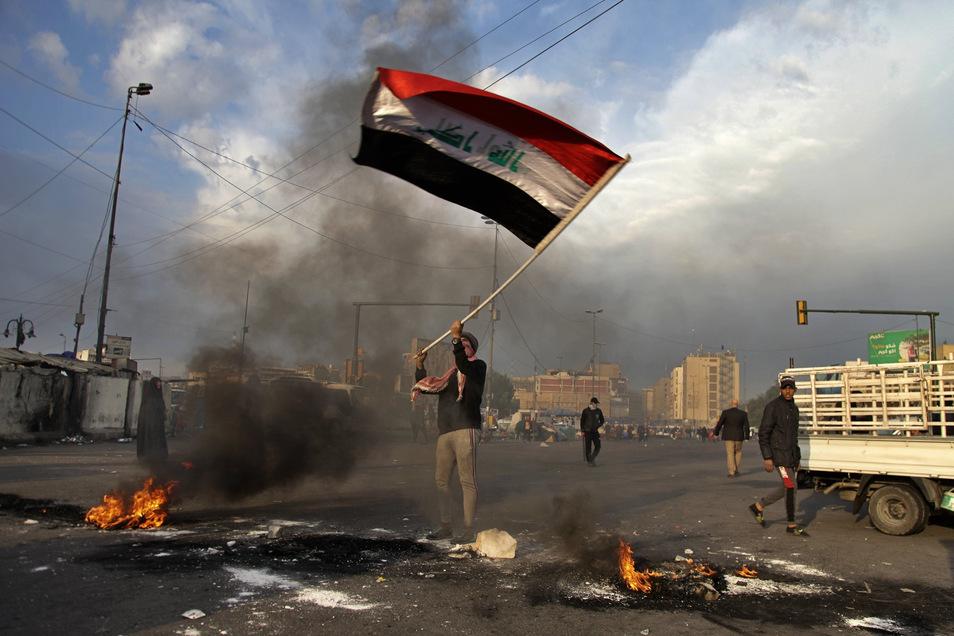 Ein Demonstrant schwenkt während eines Protests gegen den iranischen Raketenangriffe auf US-Stützpunkte im Irak in der Nähe des Tahrir-Platzes eine irakische Flagge.