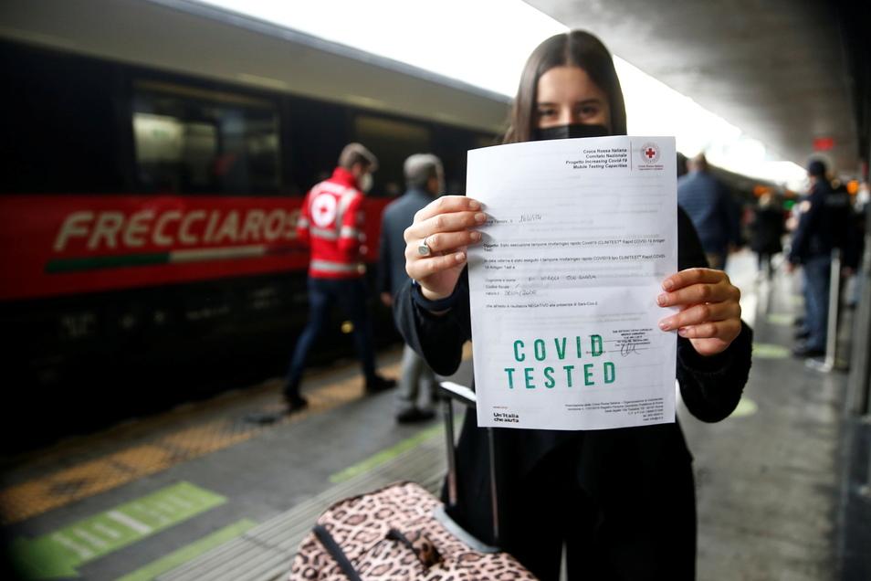 Eine Frau hält am Hauptbahnhof Termini in Rom ein Zertifikat, das ihren Corona-Test bescheinig. Nur mit der darf sie den Zug nach Mailand nehmen.