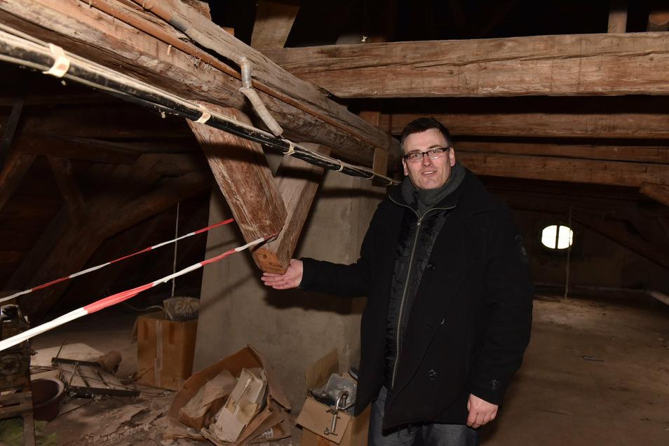 Konstantin Hermann zeigt hier auf dem Dachboden eine Stelle, wo ein Sparren herausgesägt worden ist. Solche Schäden will er wieder reparieren.