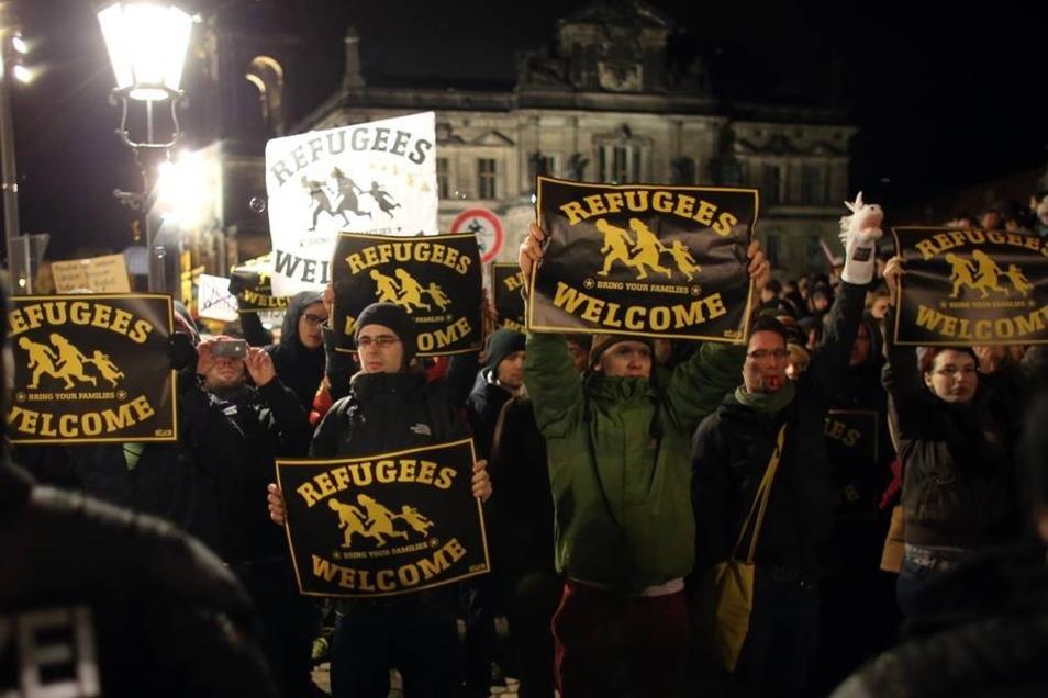 """""""Refugees welcome"""" (Flüchtlinge willkommen) steht auf Plakaten, die Teilnehmer der Gegen-Kundgebung von """"Bündnis Nazifrei"""" auf dem Schlossplatz tragen. Sie wenden sich damit klar gegen das Hauptanliegen von Pegida."""