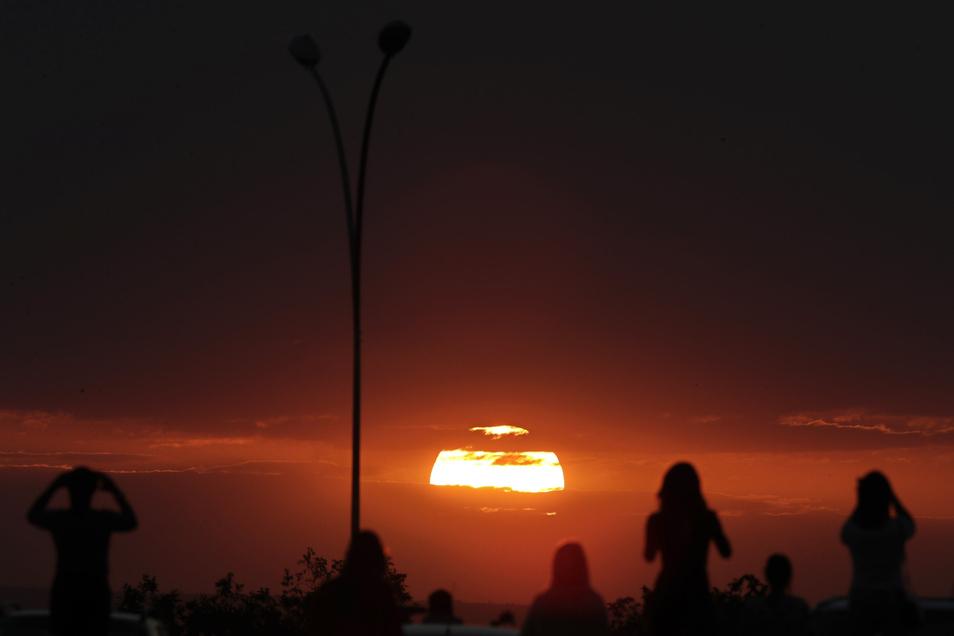 In Brasilien beobachteten Menschen den Sonnenuntergang im Vorfeld einer partiellen Mondfinsternis.