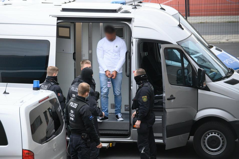 Teil einer spektakulären Polizeiaktion: Ein Verdächtiger im Fall um den Kunstdiebstahl im Grünen Gewölbe wird von Polizisten in das Gebäude des Dresdner Oberlandesgerichts.