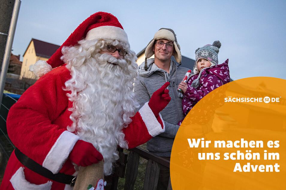 Weihnachtsmann Bernd Richter überrascht die zweijährige Hanna mit Papa Marcus Grille.
