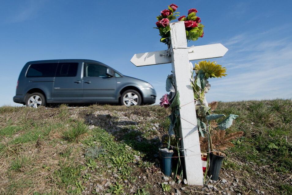 Ein Kreuz zum Gedenken an einen Verkehrstoten steht an einer Landstraße.