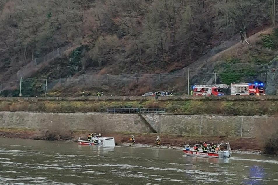 Einsatzkräfte der Feuerwehr und Wasserschutzpolizei sind an einem Wohnmobil im Einsatz, nachdem ein Mann über eine Fährrampe hinaus damit in den Rhein gefahren ist. Der Fahrer wurde durch die Dachluke gerettet.