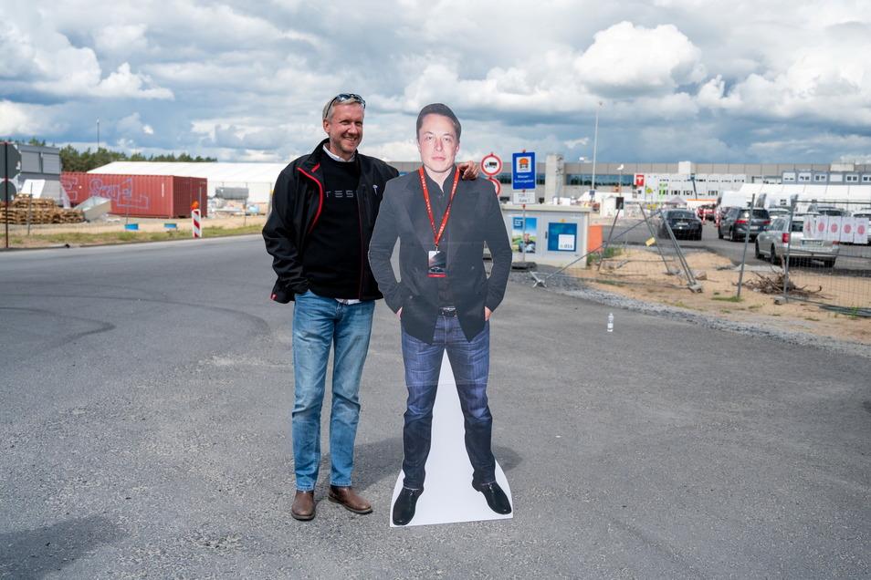 Tesla-Fan Martin Wrobel steht mit einem Pappaufsteller von Elon Musk vor der Tesla Gigafactory.