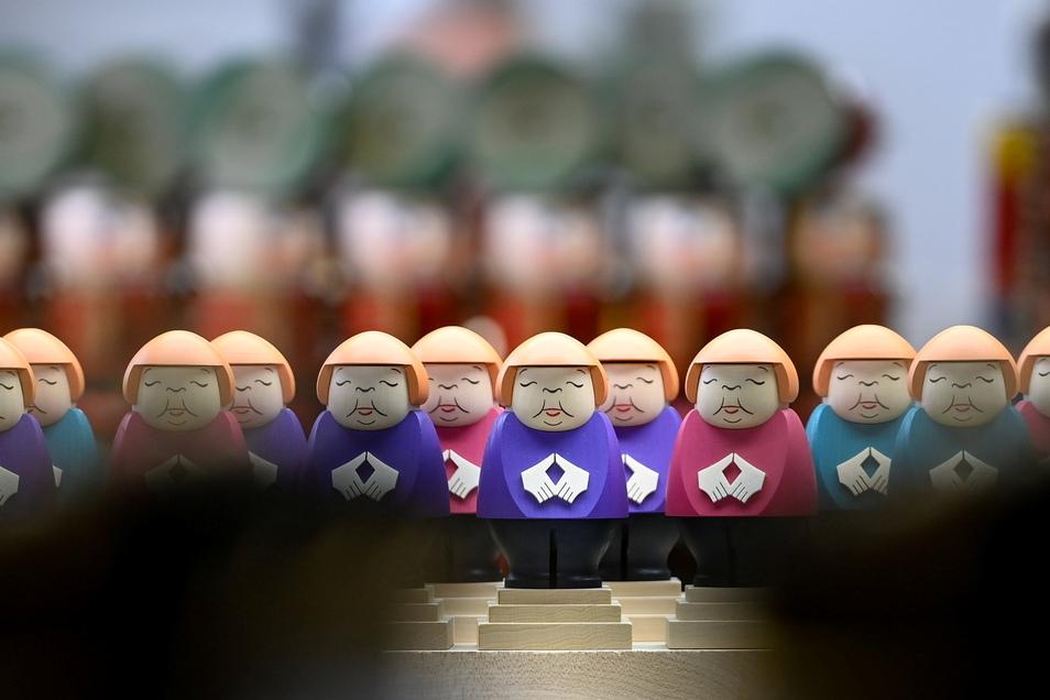 Die scheidende Kanzlerin kommt mit Merkel-Raute und wahlweise in einem Blazer in rosa, türkis oder violett daher.