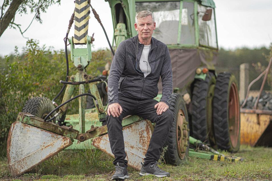 """Uwe Herwehe freut sich über das 30. Jubiläum seiner Tiefbaufirma in Kamenz. Seinen allerersten Bagger, einen T 157, hat er immer noch zur Deko auf dem Gelände stehen. Der wird im Volksmund auch  """"Zwiebelzieher"""" genannt."""