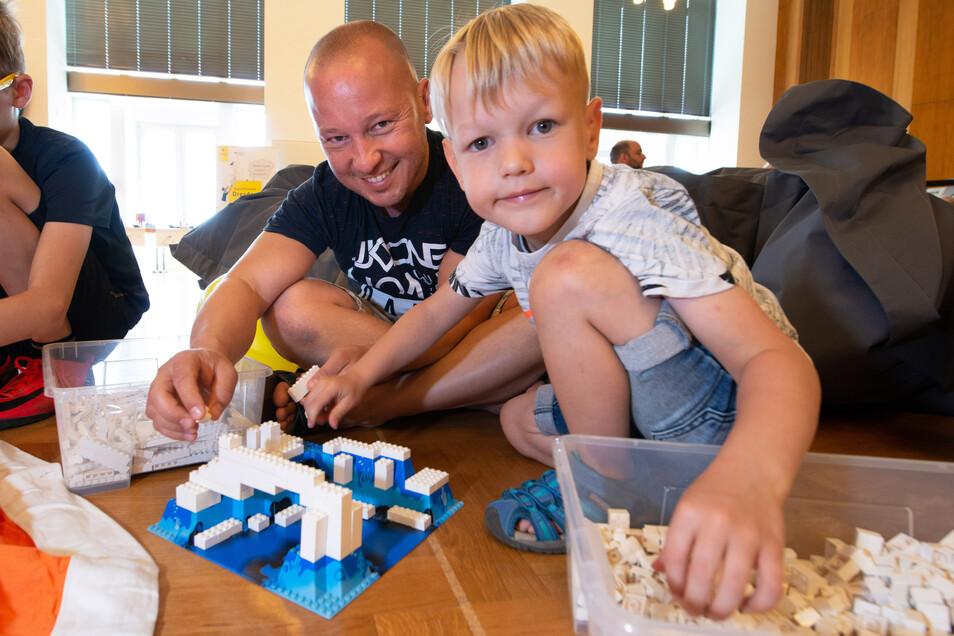 Elias (4) baut mit Papa Chris-David Scholz einen Fluss aus Lego im Festsaal des Rathauses.