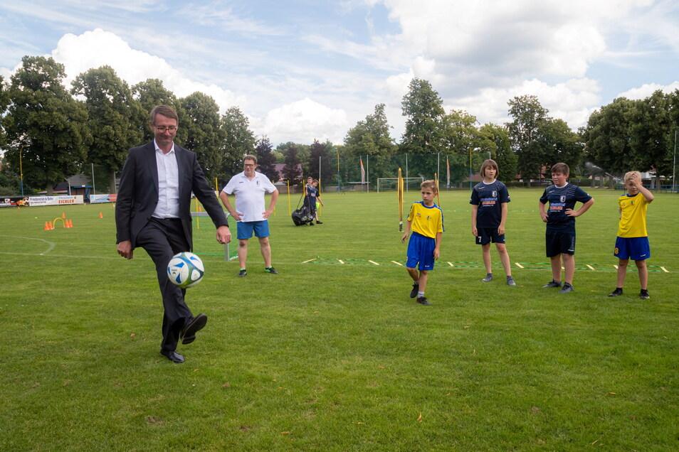 Roland Wöller ist als Innenminister auch für den Sport im Freistaat zuständig und nutzt den Termin in Rothenburg, um sich im Beisein der Nachwuchskicker selbst am Ball zu versuchen.