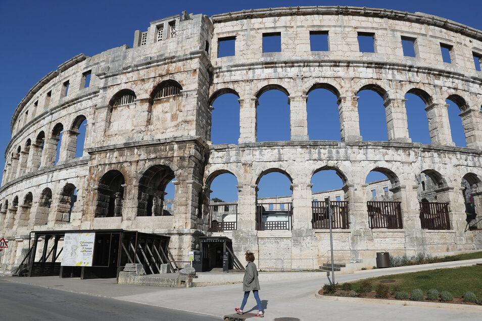 Eine arbeitslose Fremdenführerin geht am römischen Amphitheater in Pula vorbei. Dort drängen sich normalerweise Touristen. Wegen der Corona-Beschränkungen ist das Amphitheater geschlossen.