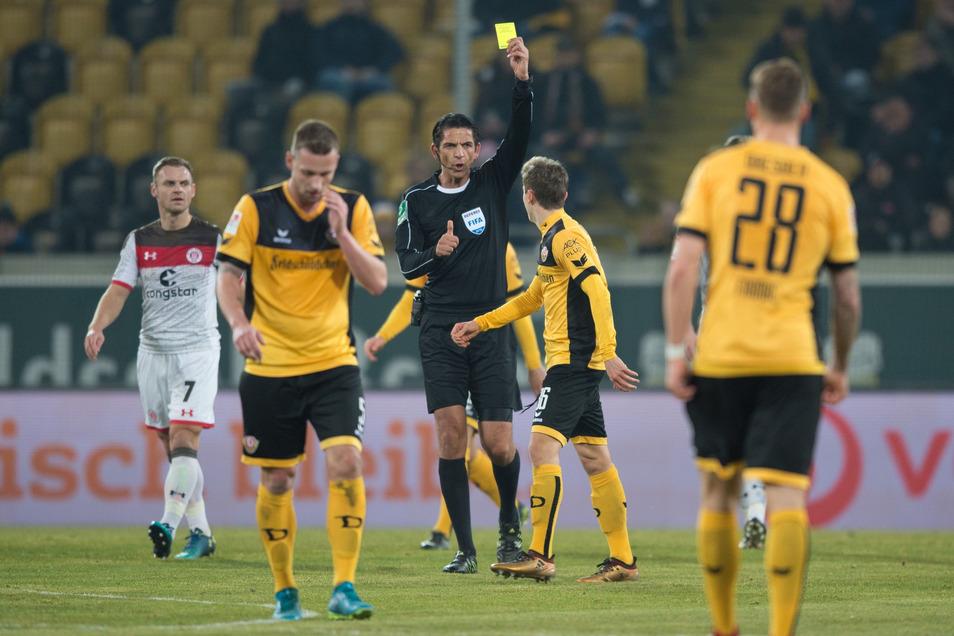 Ein Bild vom Januar 2018: Schiedsrichter Deniz Aytekin (M.) zeigt Dynamos Niklas Hauptmann (2. v. r.) die Gelbe Karte. Damals wurde der Videobeweis in der 2. Bundesliga noch nicht angewendet.