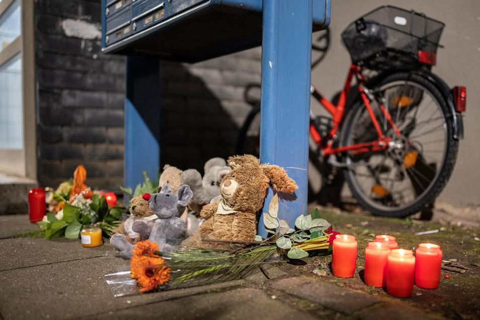 Teddybären, Kerzen und Blumen liegen und stehen vor einem Haus.