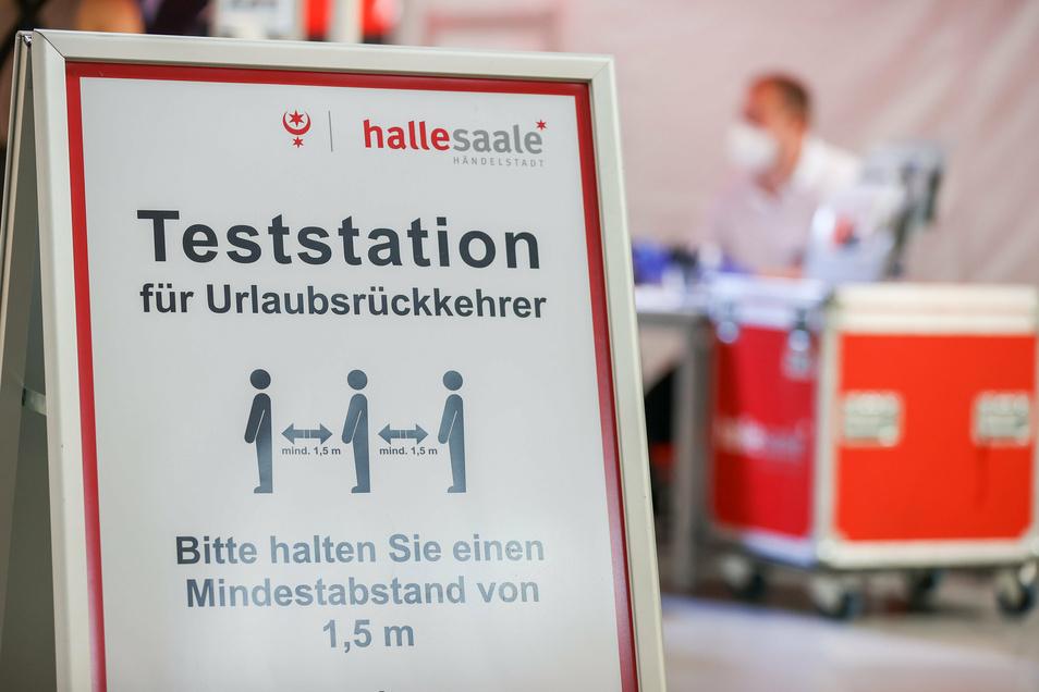 Ein Rettungsassistent der Berufsfeuerwehr Halle sitzt in einer Corona-Teststation für Urlaubsrückkehrer am Flughafen Leipzig/Halle. An der Station im Ankunftsbereich können sich ausschließlich Bewohner der Stadt Halle auf das Coronavirus testen lassen