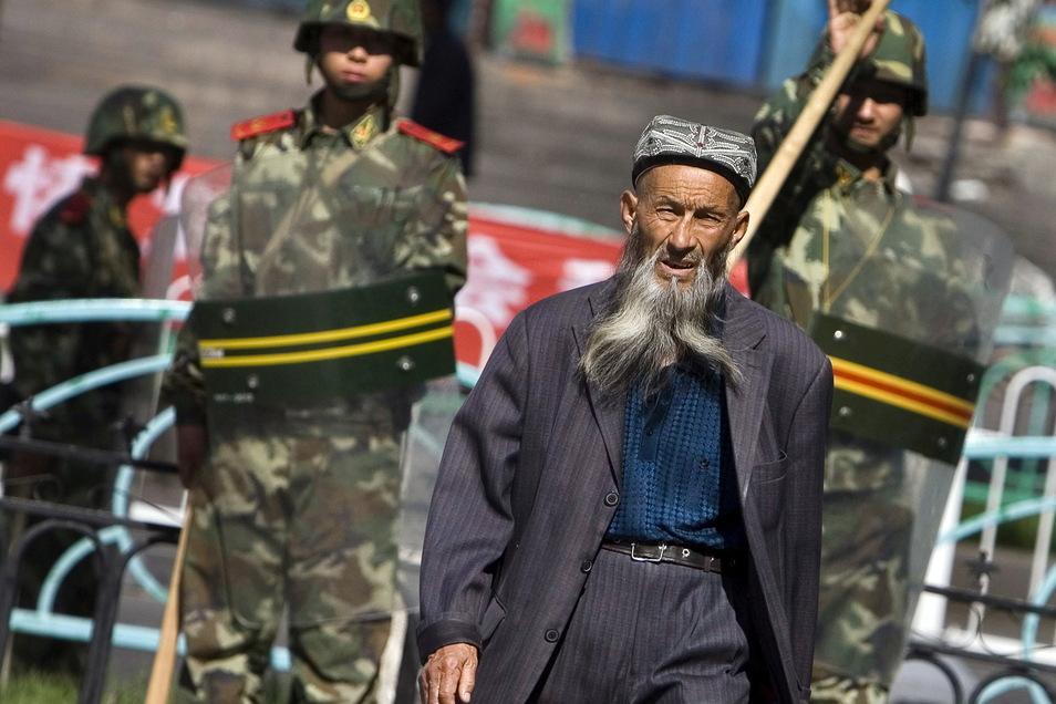 Ein Angehöriger der uigurischen Minderheit in China geht in Ürümqi in der Unruheregion Xinjiang in Nordwestchina vorbei an chinesischen Sicherheitskräften.