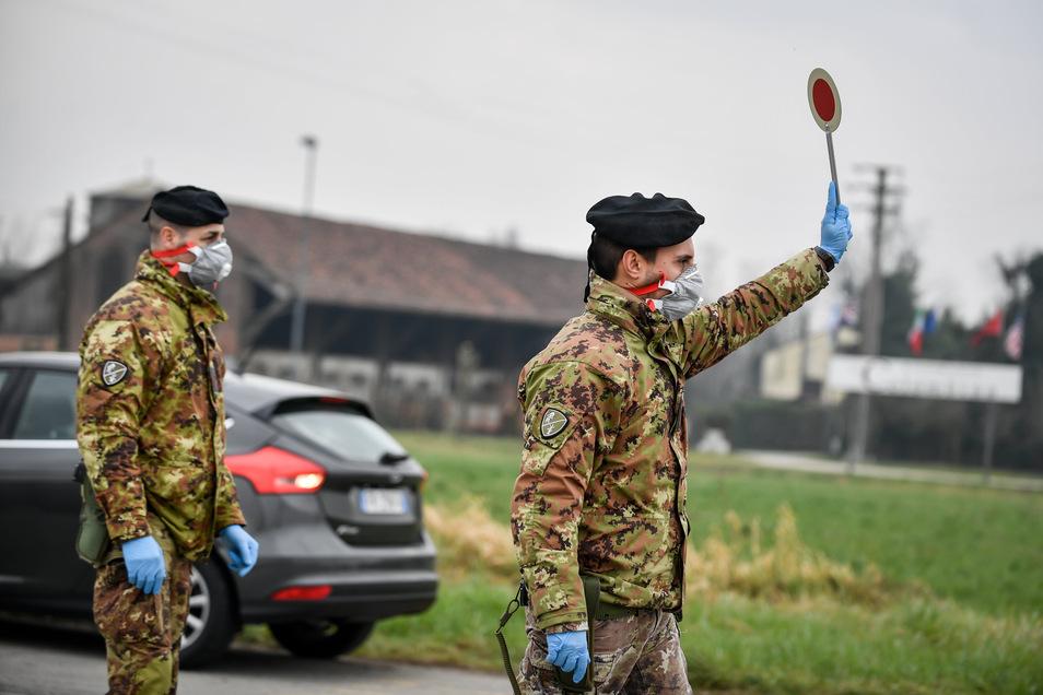 Ein Soldat hält an einer Straßensperre vor der roten Zone von Turano Lodigiano (Italien) eine Winkerkelle in die Höhe. Solche Szenarien sind auch in Deutschland im Fall einer Epidemie möglich.