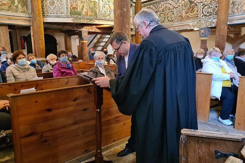 Im Bild zu sehen sind Superintendent Dr. Thomas Koppehl (im Talar) und der Präses der Synode des Kirchenkreises, Torsten Vogel, bei der Unterzeichnung der Schenkungsurkunden für die beiden Bäume.