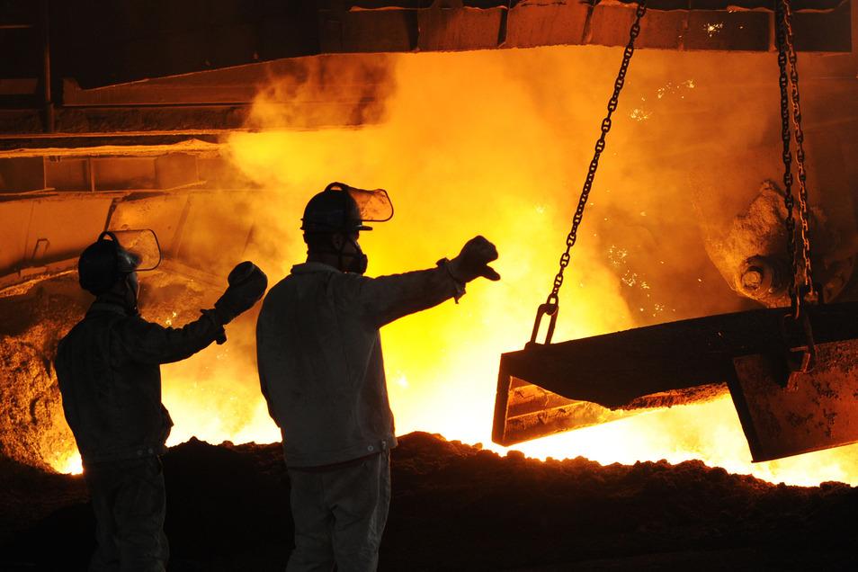 """Stahlarbeiter in Schutzkleidung arbeiten vor einem angestochenen Hochofen in dem staatlichen Unternehmen """"Dongbei Special Steel""""."""