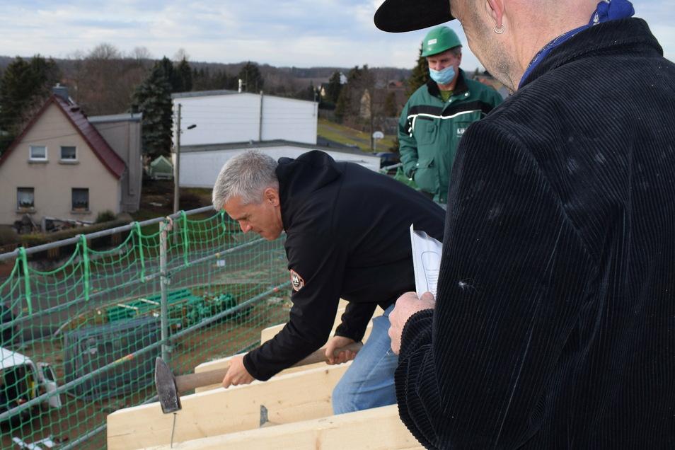 Als Bauherr schlägt Grimmas Bürgermeister Berger den letzten Nagel in den Dachstuhl ein.