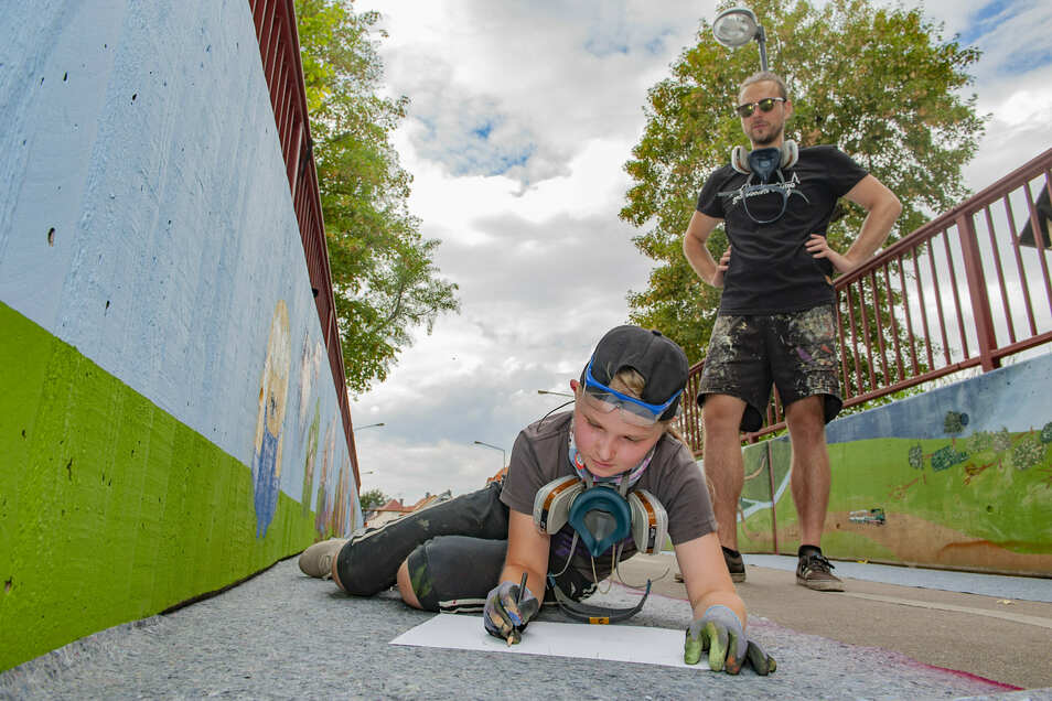 """Victoria und Marc Tuckermann bereiten ein Bild für die Wand vor zum Thema """"verrückte Stadt""""."""