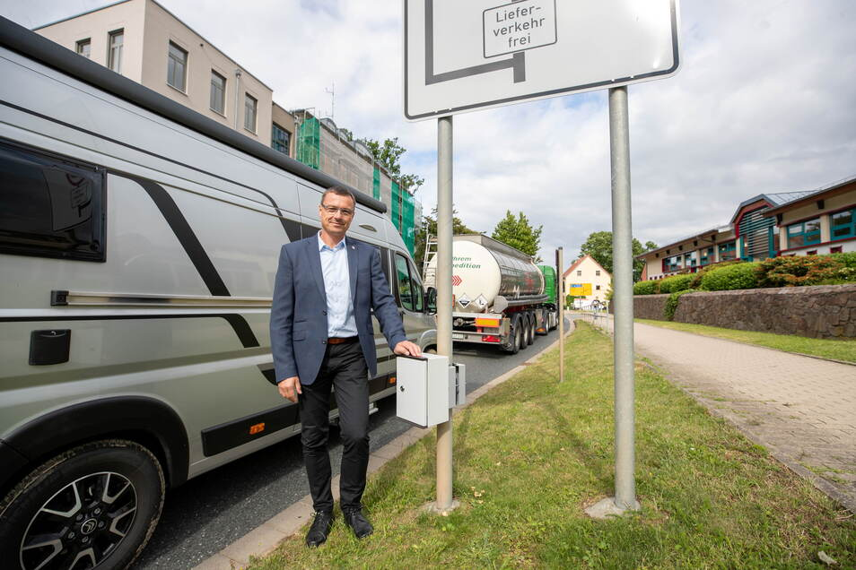 Wilsdruffs Bürgermeister Ralf Rother zeigt den Zählkasten an der Nossener Straße in Wilsdruff, der seit April dort hängt und die Zahl der Lkws und Pkws erfasst.