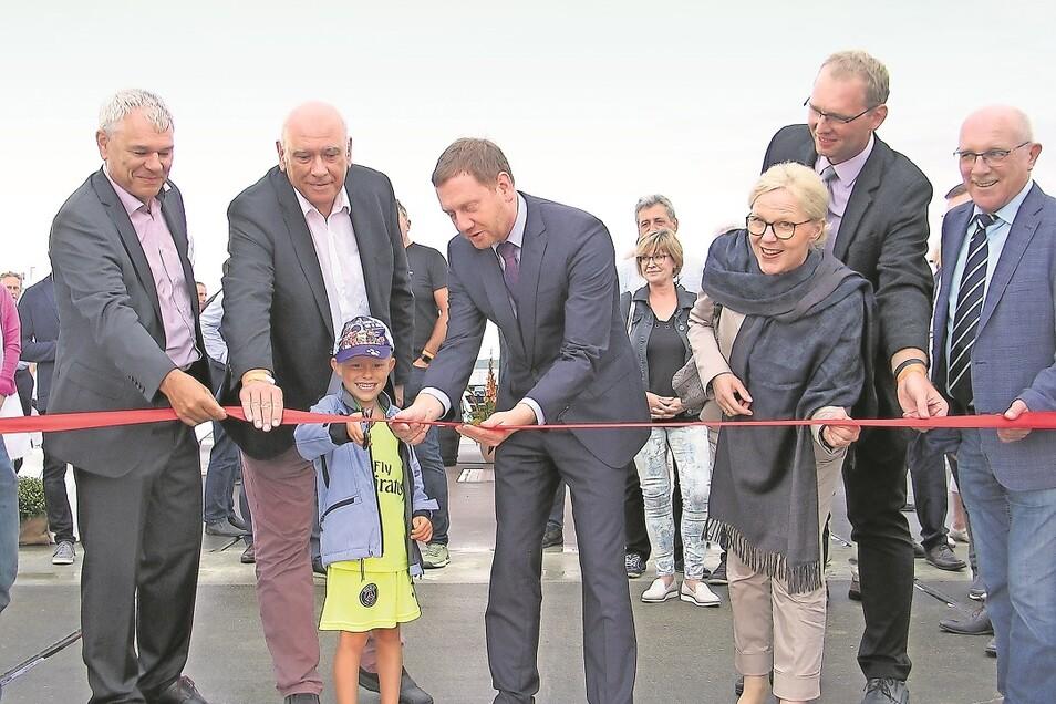 Willy, jüngster Sohn von Familie Schicke, zerschneidet zusammen mit Ministerpräsident Michael Kretschmer (M.) und weiteren Ehrengästen das symbolische Band.