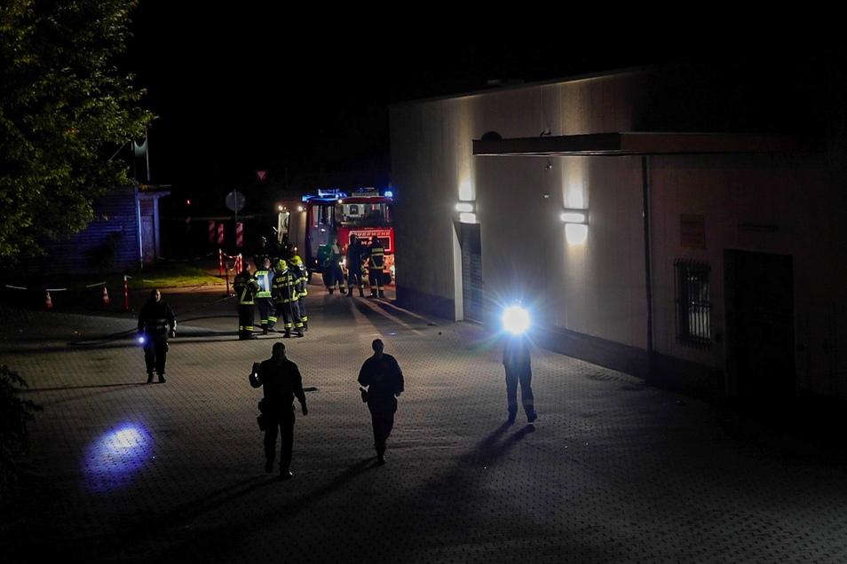 Mit Taschenlampen such Polizeibeamte das Areal um das Impfzentrum nach Spuren ab.