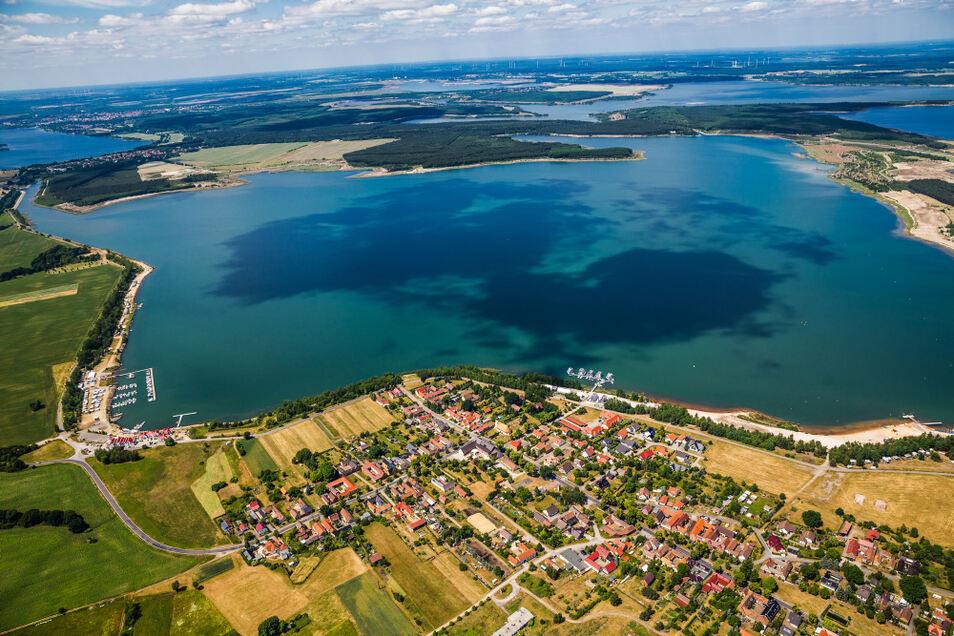 Auf diesem Luftbild ist fast der komplette Geierswalder See zu erkennen. Die linke Uferseite wird als die Südböschung bezeichnet. Seit 2015, als diese Aufnahme entstanden ist, hat sich baulich schon einiges getan.