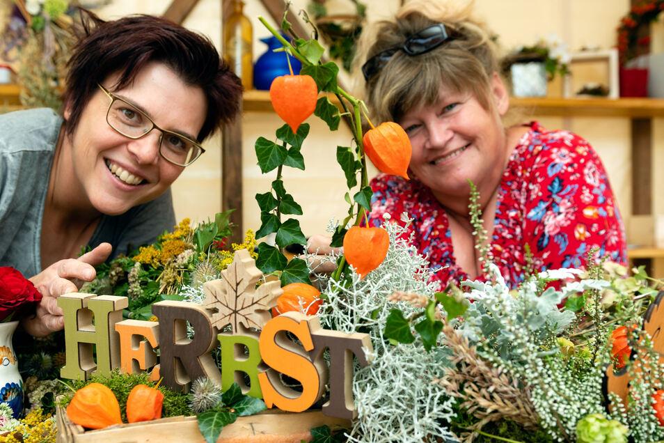 Dina Deus (links) und Elke Neumann haben nicht nur ihren Stand schön dekoriert. Sie bieten herbstliche Floristik an. Damit bleibt die gute Laune noch eine Weile erhalten.