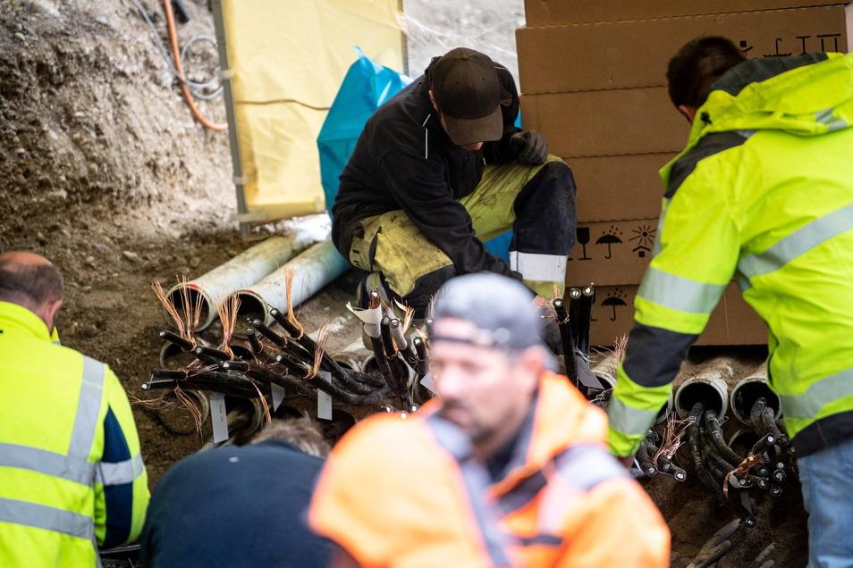 Bayern, München: Arbeiter reparieren an einer Baustelle, an der ein Kabelbrand ausgebrochen war, die Leitungen.