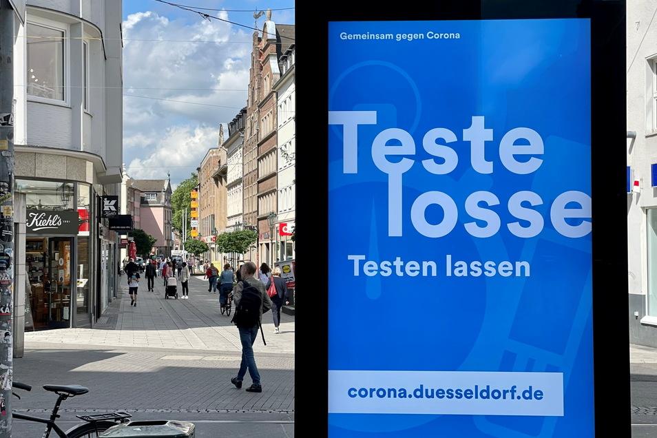 Ein digitales Werbeplakat fordert in rheinischer Mundart in der Düsseldorfer Altstadt zum Covid 19-Testen auf.