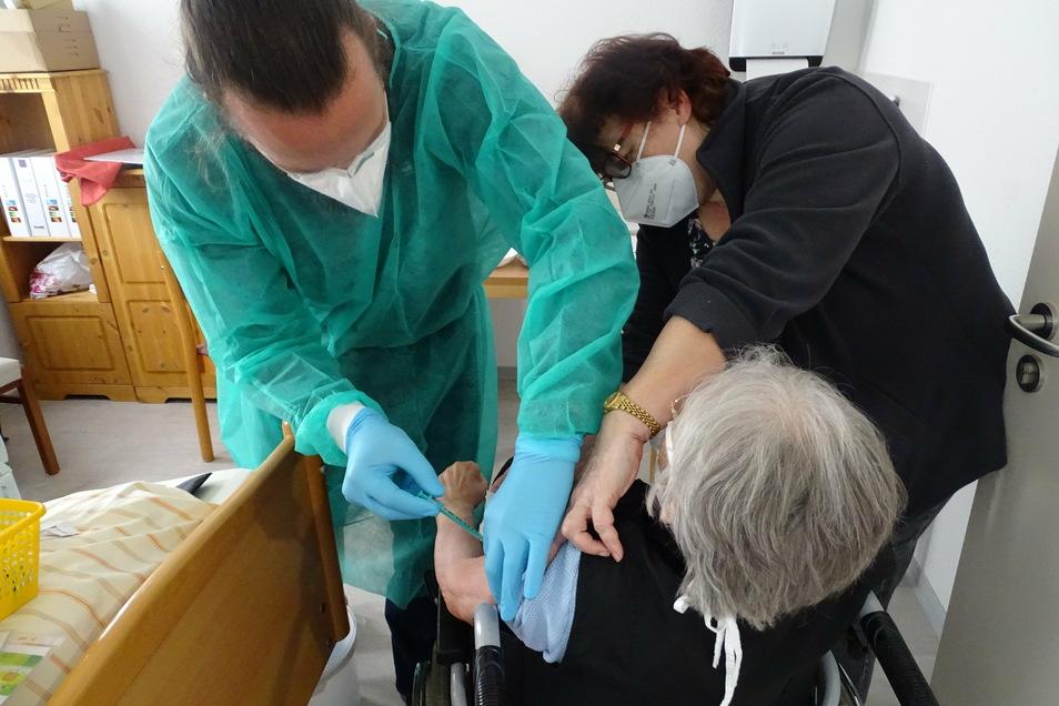 Dr. Mark Steinle (links) von der Uniklinik Dresden impft eine Bewohnerin des ASB Pflege- und Betreuungszentrum Weidenblick Gröditz.